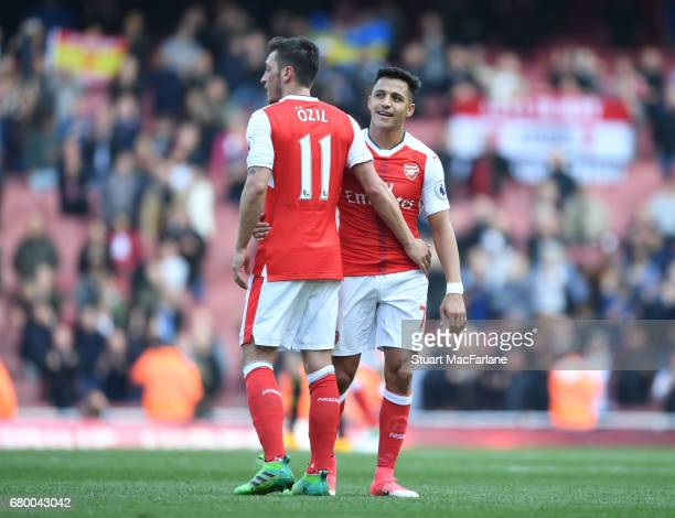 Mesut Ozil and Alexis Sanchez of Arsenal during the Premier League match between Arsenal and Manchester United at Emirates Stadium on May 7 2017 in...