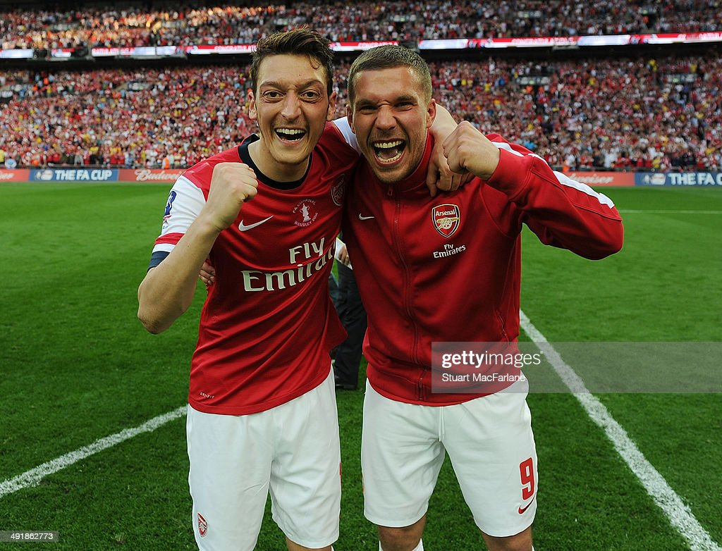 Mesut Ozil and <a gi-track='captionPersonalityLinkClicked' href=/galleries/search?phrase=Lukas+Podolski&family=editorial&specificpeople=204460 ng-click='$event.stopPropagation()'>Lukas Podolski</a> of Arsenal celebrate after the FA Cup Final between Arsenal and Hull City at Wembley Stadium on May 17, 2014 in London, England.