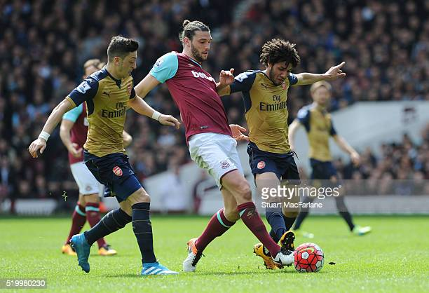 Mesut Ozil and Mohamed Elneny of Arsenal challenge Andy Carroll of West Ham during the Barclays Premier League match between West Ham United and...