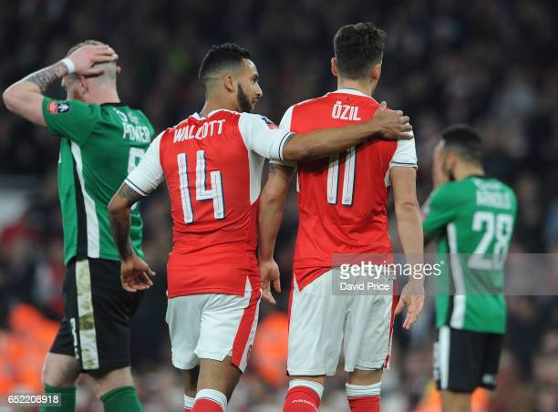 Mesut Ozil and Theo Walcott celebrate Arsenal's 3rd goal during the match between Arsenal and Lincoln City at Emirates Stadium on March 11 2017 in...