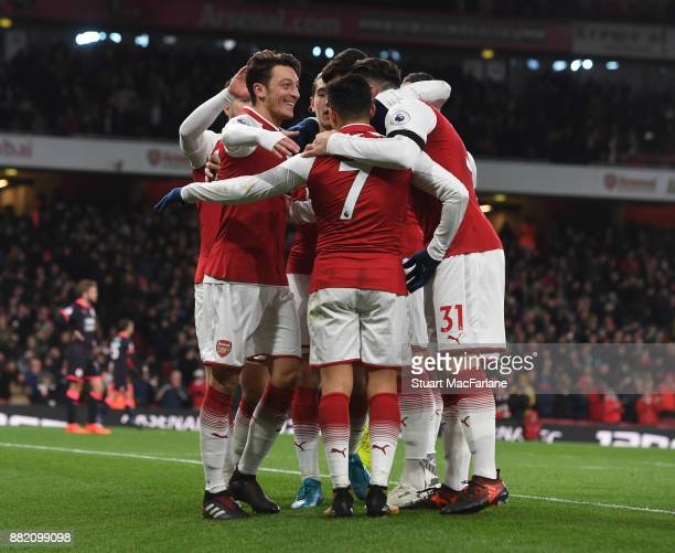 Mesut Ozil celebrates Arsenal's 3rd goal scored by Alexis Sanchez during the Premier League match between Arsenal and Huddersfield Town at Emirates...