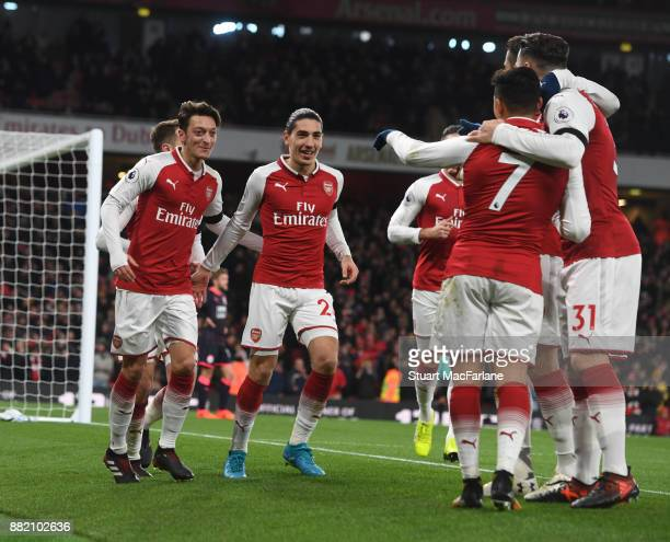 Mesut Ozil celebrates Arsenal's 3rd goal scored by Alexis Sanchez with Hector Bellerin during the Premier League match between Arsenal and...
