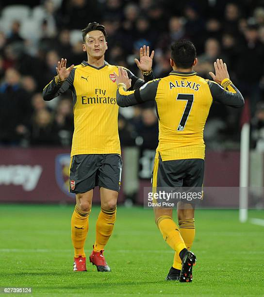 Mesut Ozil celebrates scoring a goal for Arsenal with Alexis Sanchez during the Premier League match between West Ham United and Arsenal at London...