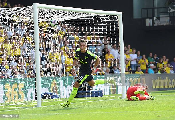Mesut Ozil celebrates scoring Arsenal's 3rd goal during the Premier League match between Watford and Arsenal at Vicarage Road on August 27 2016 in...