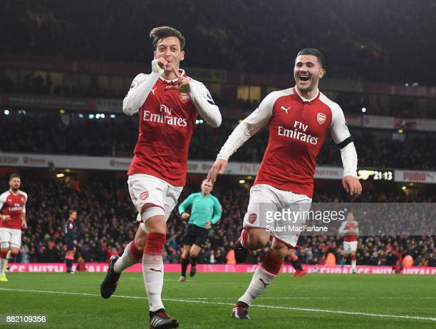 Mesut Ozil celebrates scoring the 4th Arsenal goal with Sead Kolasinac during the Premier League match between Arsenal and Huddersfield Town at...