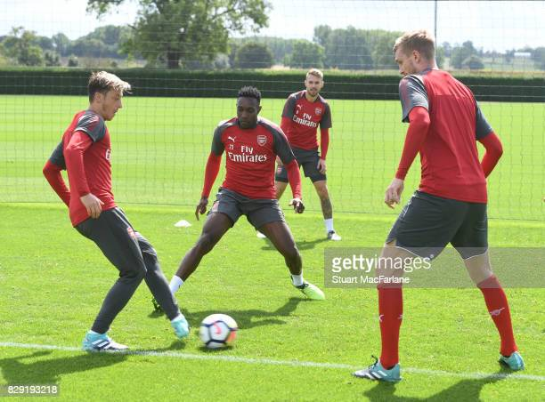 Mesut Ozil Danny Welbeck and Per Mertesacker of Arsenal during a training session at London Colney on August 10 2017 in St Albans England