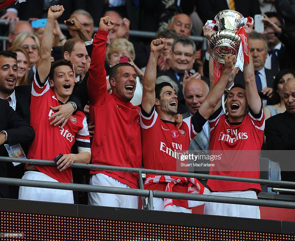 Mesut Ozil Lukas Podolski Mikel Arteta and Thomas Vermaelen lift the FA Cup after the FA Cup Final between Arsenal and Hull City at Wembley Stadium...