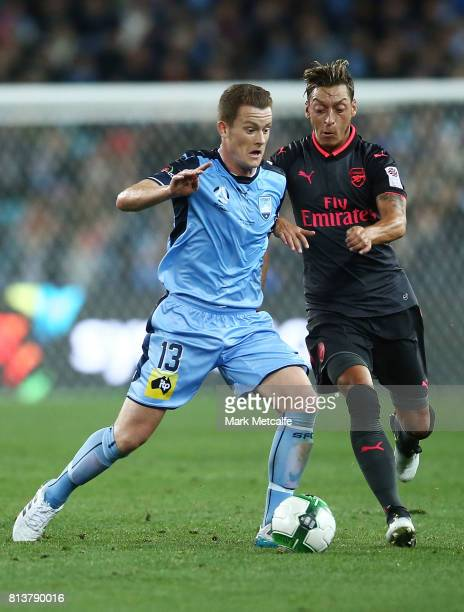 Mesut Ozil of Arsenal and Brandon O'Neill of Sydney FC compete during the match between Sydney FC and Arsenal FC at ANZ Stadium on July 13 2017 in...