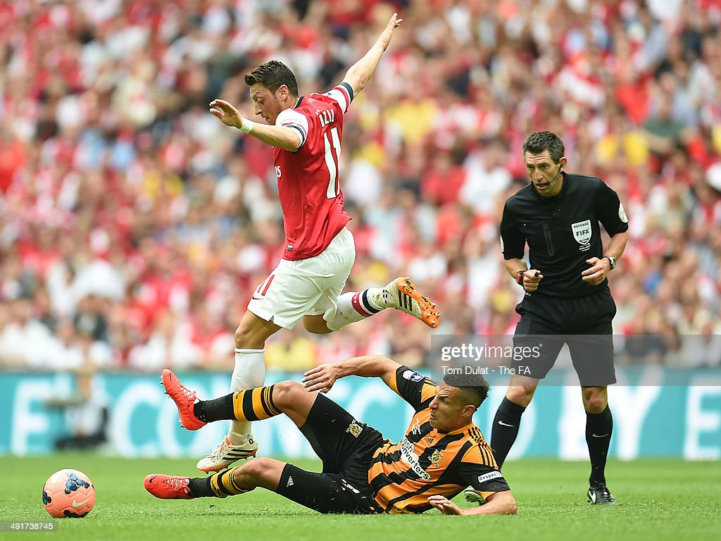 Mesut Ozil of Arsenal and Jake Livermore of Hull City battle for the ball during the FA Cup with Budweiser Final match between Arsenal and Hull City at Wembley Stadium on May 17, 2014 in London, England.