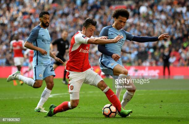 Mesut Ozil of Arsenal and Leroy Sane of Manchester City compete for the ball during the Emirates FA Cup SemiFinal match between Arsenal and...