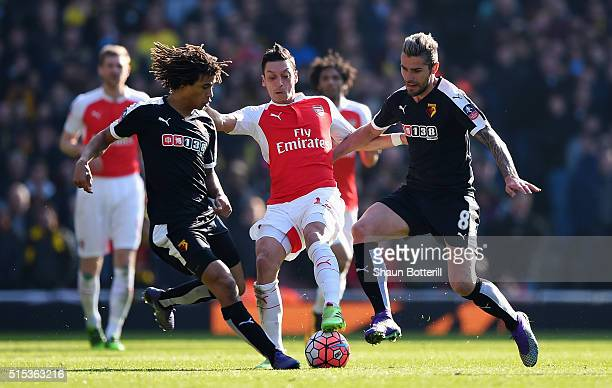 Mesut Ozil of Arsenal battles with Nathan Ake and Valon Behrami of Watford during the Emirates FA Cup sixth round match between Arsenal and Watford...