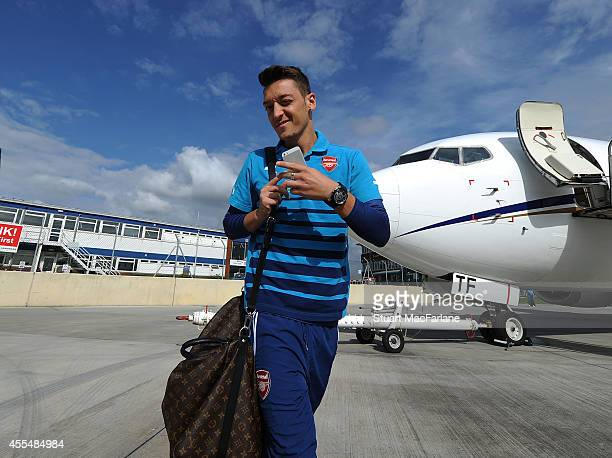 Mesut Ozil of Arsenal boards the team plane at Luton Airport on September 15 2014 in St Albans England Photo by Stuart MacFarlane/Arsenal FC via...