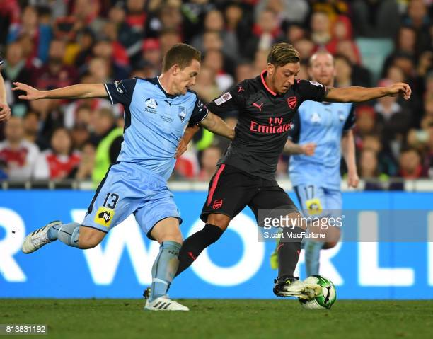 Mesut Ozil of Arsenal breaks past Brandon O'Neill of Sydney FC during the preseason friendly match between Sydney FC and Arsenal at ANZ Stadium on...
