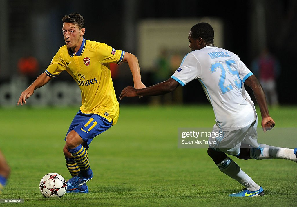 Mesut Ozil of Arsenal breaks past <a gi-track='captionPersonalityLinkClicked' href=/galleries/search?phrase=Giannelli+Imbula&family=editorial&specificpeople=11355911 ng-click='$event.stopPropagation()'>Giannelli Imbula</a> of Marseille during the match at Stade Velodrome on September 18, 2013 in Marseille, France.