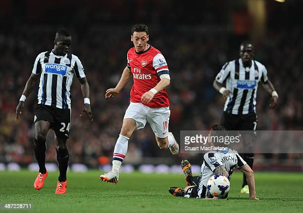 Mesut Ozil of Arsenal breaks past Mathieu Debuchy who has fallen to the turf and Cheick Tiote of Newcastle during the Barclays Premier League match...