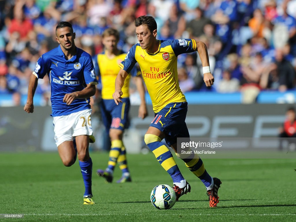 Mesut Ozil of Arsenal breaks past Riyad Mahrez of Leicester during the Barclays Premier League match between Leicester City and Arsenal at The King Power Stadium on August 31, 2014 in Leicester, England.