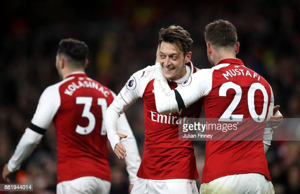 Mesut Ozil of Arsenal celebrates after scoring his sides fourth goal with Shkodran Mustafi of Arsenal during the Premier League match between Arsenal...