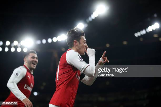 Mesut Ozil of Arsenal celebrates after scoring his sides fourth goal during the Premier League match between Arsenal and Huddersfield Town at...