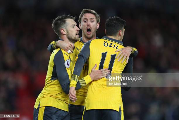 Mesut Ozil of Arsenal celebrates as he scores their second goal with Aaron Ramsey and Nacho Monreal during the Premier League match between...