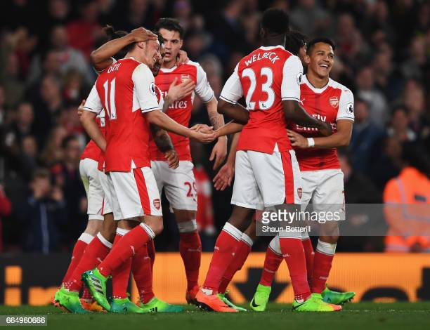 Mesut Ozil of Arsenal celebrates scoring his sides first goal with his Arsenal team mates during the Premier League match between Arsenal and West...