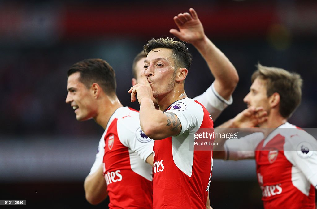 Mesut Ozil of Arsenal (C) celebrates scoring his sides third goal with his team mates during the Premier League match between Arsenal and Chelsea at the Emirates Stadium on September 24, 2016 in London, England.