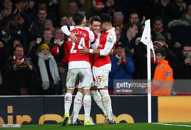 Mesut Ozil of Arsenal celebrates scoring his team's second goal with his team mates Alex OxladeChamberlain and Hector Bellerin during the Barclays...