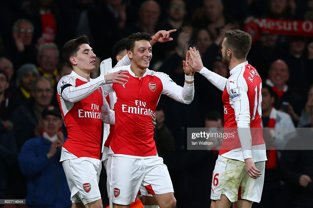 Mesut Ozil (C) of Arsenal celebrates scoring his team's second goal with his team mates Hector Bellerin (L) and <a gi-track='captionPersonalityLinkClicked' href=/galleries/search?phrase=Aaron+Ramsey&family=editorial&specificpeople=4784114 ng-click='$event.stopPropagation()'>Aaron Ramsey</a> (R) during the Barclays Premier League match between Arsenal and A.F.C. Bournemouth at Emirates Stadium on December 28, 2015 in London, England.