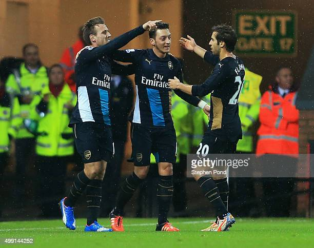 Mesut Ozil of Arsenal celebrates with team mates Nacho Monreal and Mathieu Flamini as he scores their first goal during the Barclays Premier League...