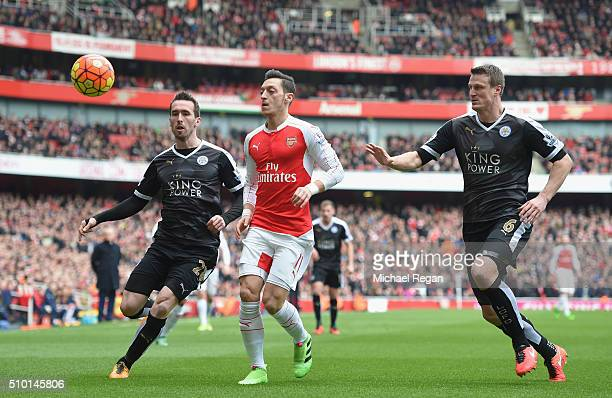 Mesut Ozil of Arsenal challanges Robert Huth of Leicester City and Christian Fuchs of Leicester City during the Barclays Premier League match between...
