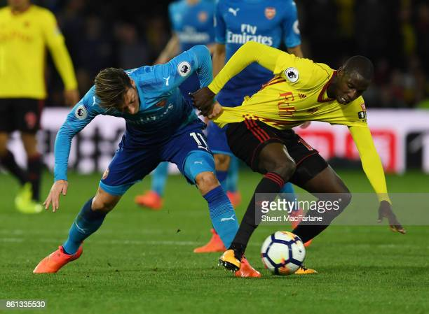 Mesut Ozil of Arsenal challenged by Abdouaye Doucoure of Watford during the Premier League match between Watford and Arsenal at Vicarage Road on...