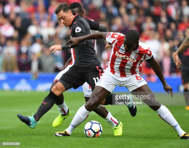 Mesut Ozil of Arsenal challenged by Kurt Zouma of Stoke during the Premier League match between Stoke City and Arsenal at Bet365 Stadium on August 19...