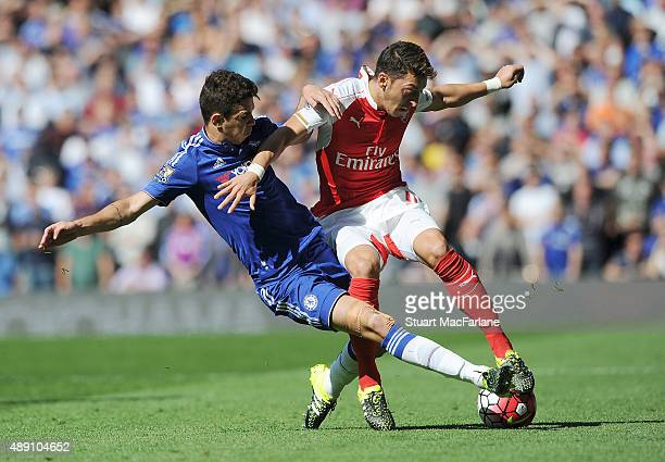 Mesut Ozil of Arsenal challenged by Oscar of Chelsea during the Barclays Premier League match between Chelsea and Arsenal on September 19 2015 in...