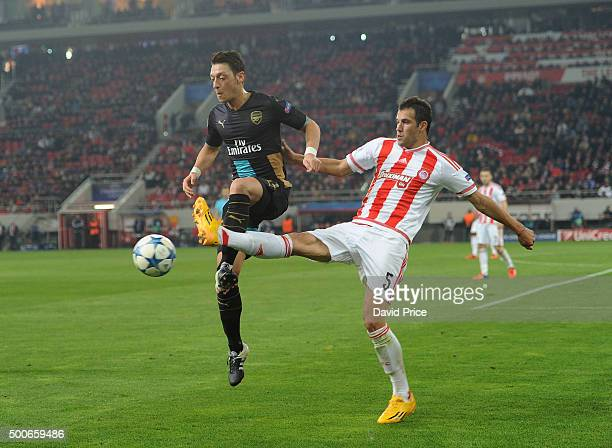Mesut Ozil of Arsenal controls the ball under pressure from Luka Milivojevic of Olympiacos during the UEFA Champions League group F stage match...