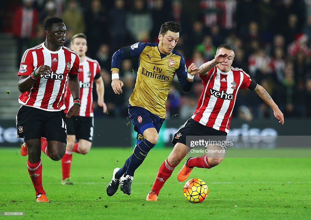 Mesut Ozil of Arsenal goes between <a gi-track='captionPersonalityLinkClicked' href=/galleries/search?phrase=Victor+Wanyama&family=editorial&specificpeople=7126412 ng-click='$event.stopPropagation()'>Victor Wanyama</a> and <a gi-track='captionPersonalityLinkClicked' href=/galleries/search?phrase=Jordy+Clasie&family=editorial&specificpeople=7012011 ng-click='$event.stopPropagation()'>Jordy Clasie</a> of Southampton during the Barclays Premier League match between Southampton and Arsenal at St Mary's Stadium on December 26, 2015 in Southampton, England.