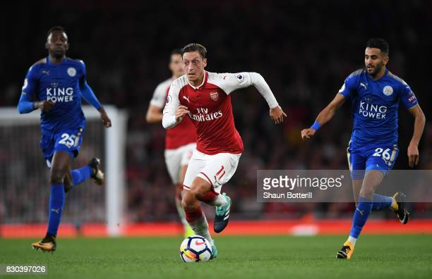 Mesut Ozil of Arsenal goes past Wilfred Ndidi and Riyad Mahrez of Leicester City during the Premier League match between Arsenal and Leicester City...