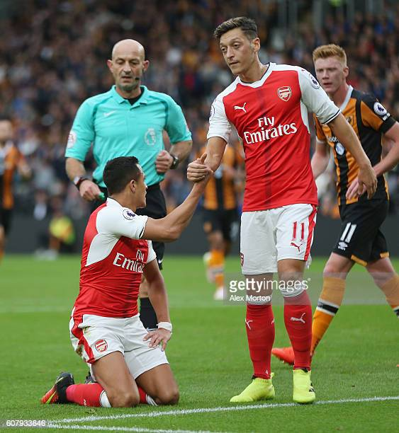 Mesut Ozil of Arsenal helps up team mae Alexis Sanchez during the Premier League match between Hull City and Arsenal at KCOM Stadium on September 17...