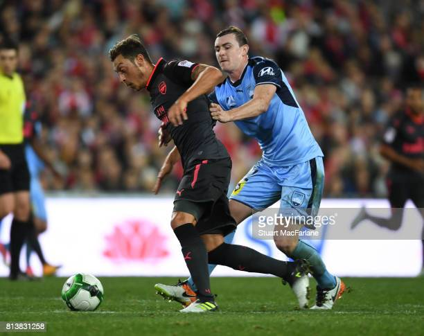 Mesut Ozil of Arsenal holds off Brandon O'Neill of Sydney FC during the preseason friendly match between Sydney FC and Arsenal at ANZ Stadium on July...