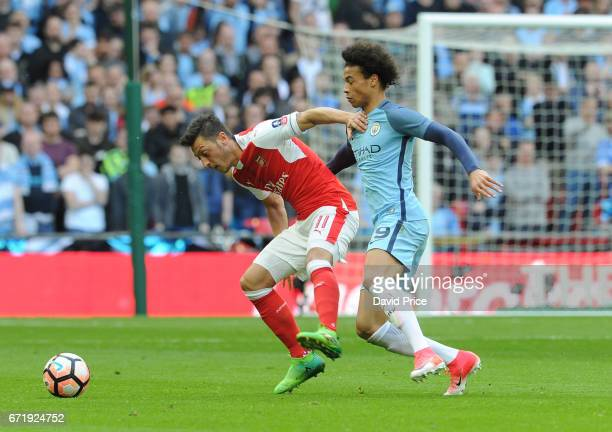 Mesut Ozil of Arsenal holds off Leroy Sane of Manchester City during the match between Arsenal and Manchester City at Wembley Stadium on April 23...