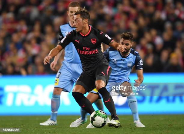 Mesut Ozil of Arsenal holds off Michael Zullo of Sydney Fcduring the preseason friendly match between Sydney FC and Arsenal at ANZ Stadium on July 13...