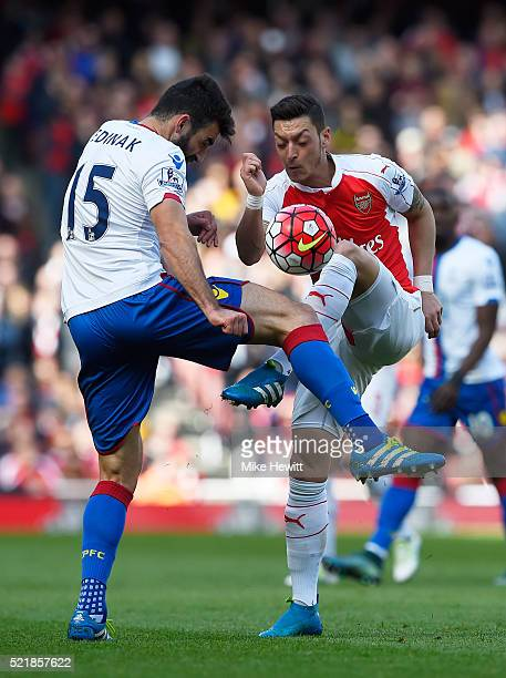 Mesut Ozil of Arsenal holds off pressure from Mile Jedinak of Crystal Palace during the Barclays Premier League match between Arsenal and Crystal...