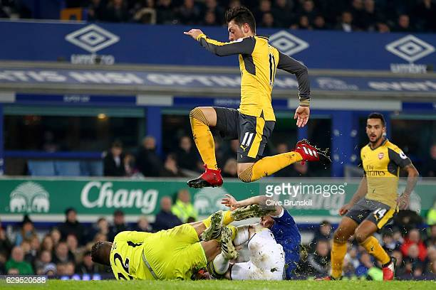 Mesut Ozil of Arsenal hurdles colliding teammates Maarten Stekelenburg and Leighton Baines of Everton during the Premier League match between Everton...