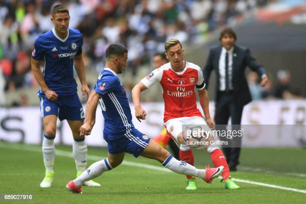 Mesut Ozil of Arsenal is challenged by Eden Hazard of Chelsea during The Emirates FA Cup Final between Arsenal and Chelsea at Wembley Stadium on May...