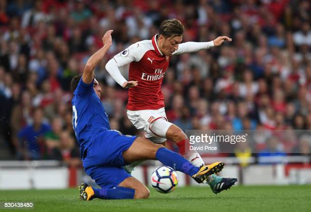 Mesut Ozil of Arsenal is challenged by Matty James of Leicester during the Premier League match between Arsenal and Leicester City at Emirates...