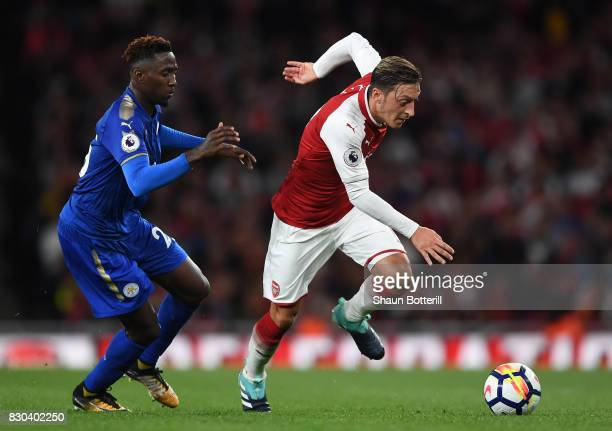 Mesut Ozil of Arsenal is challenged by Wilfred Ndidi of Leicester City during the Premier League match between Arsenal and Leicester City at the...