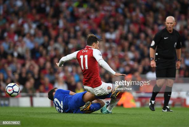 Mesut Ozil of Arsenal is fouled by Matty James of Leicester during the Premier League match between Arsenal and Leicester City at Emirates Stadium on...