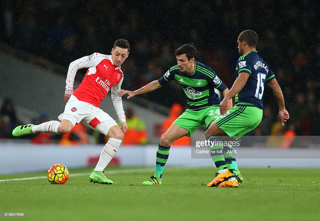 Mesut Ozil of Arsenal is marked by <a gi-track='captionPersonalityLinkClicked' href=/galleries/search?phrase=Jack+Cork&family=editorial&specificpeople=4206991 ng-click='$event.stopPropagation()'>Jack Cork</a> and <a gi-track='captionPersonalityLinkClicked' href=/galleries/search?phrase=Wayne+Routledge&family=editorial&specificpeople=206672 ng-click='$event.stopPropagation()'>Wayne Routledge</a> of Swansea City during the Barclays Premier League match between Arsenal and Swansea City at the Emirates Stadium on March 02, 2016 in London, England.