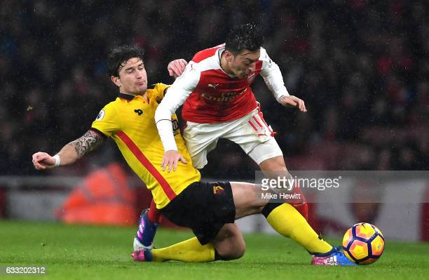 Mesut Ozil of Arsenal is tackled by Daryl Janmaat of Watford during the Premier League match between Arsenal and Watford at Emirates Stadium on...