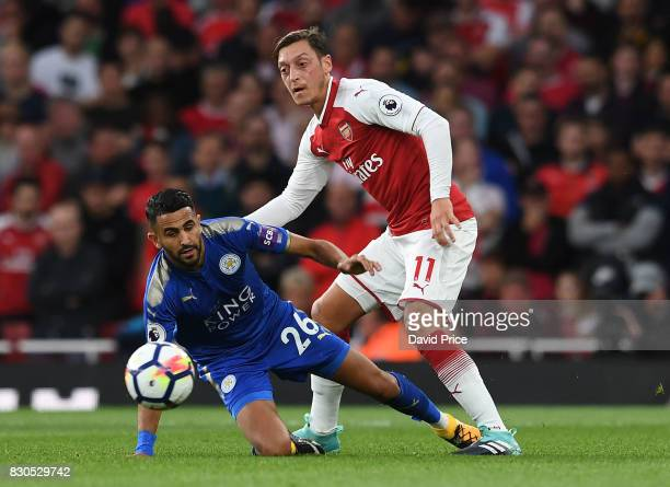 Mesut Ozil of Arsenal passes the ball under pressure from Riyad Mahrez of Leicester during the Premier League match between Arsenal and Leicester...