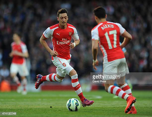 Mesut Ozil of Arsenal passes to Alexis Sanchez during the match between Arsenal and Sunderland in the Barclays Premier League at Emirates Stadium on...
