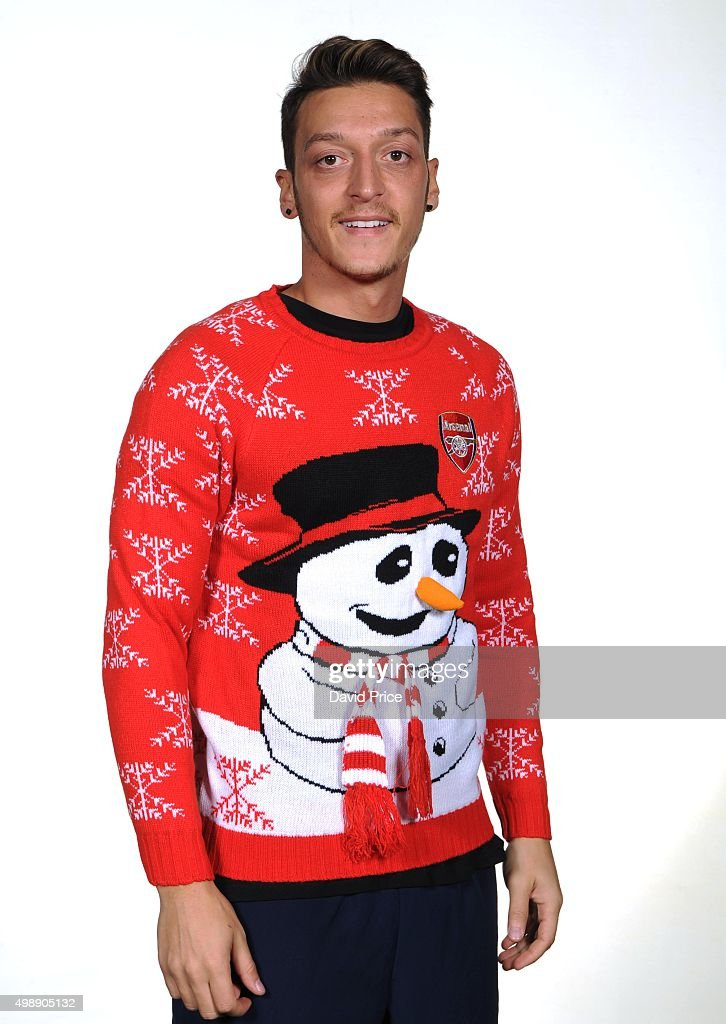 Mesut Ozil of Arsenal poses in the Arsenal Christmas Jumper during a charity photo shoot on September 30, 2015 in London, England.